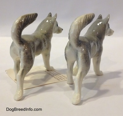 The back right side of two grey with white Husky figurines. The figurines have long glossy body