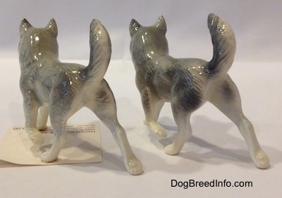 The back left side of two figurines that are Huskys with a paw in the air.