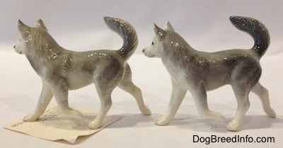 The left side of two grey and white Husky figurines with a paw in the air. Both figurines have there tails arched in the air and their ears are standing up in the air.