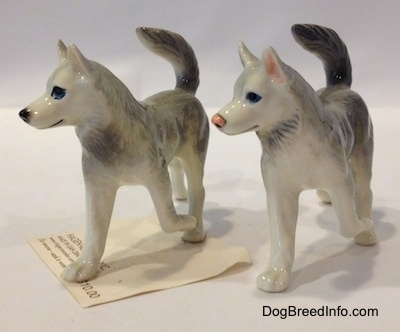 The front left side of two figurines of Huskys with a paw in the air. The figurines have black circles for eyes.