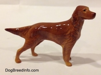 The right side of a brown Irish Setter figurine. The figurine has long legs and a hairy body.
