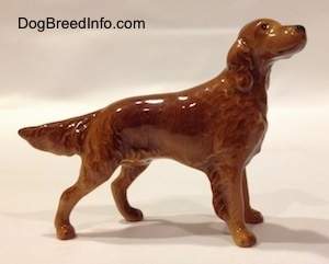 The right side of a brown Irish Setter figurine that is looking up. The tail of the figurine is lifted, but tilted towards the ground.