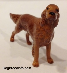 An Irish Setter figurine that has black circles for eyes and a black circle for a nose.