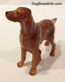 The front left side of a brown Irish Setter figurine that has its head turned to the left. It has hairy ears and its ears are hard to differentiate from its body.