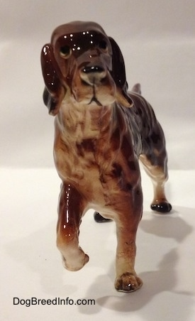 A ceramic brown with tan Irish Setter figurine pointing. The figurine has black circles for eyes.