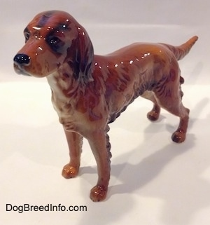 The front left side of a brown with black Irish Setter figurine. The figurine has black circles for eyes.