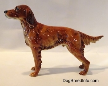 The left side of an Irish Setter figurine. The figurine has its tail out, level wth its body.