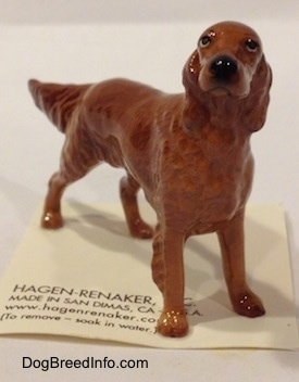 The front right side of a brown Irish Setter figurine. The figurine is looking up it has a circular black nose.