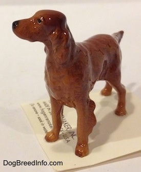 The back left side of a Irish Setter figurine. The figurine has its tail sticking out and it is level with its body.
