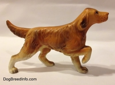 The right side of a ceramic brown with tan Irish Setter figurine with a flat finish and it is pointing.