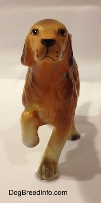 The front of a brown with tan Irish Setter ceramic figurine. The figurine is pointing and it has black spots for whiskers.