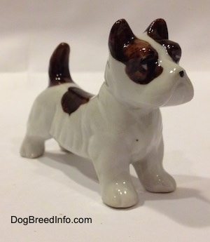 The front left side of a white with brown bone china Jack Russell Terrier dog figurine. The figurine has a black circle for a nose.