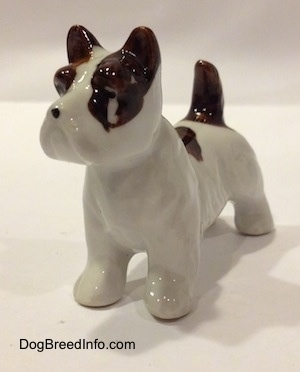 The front left side of a white with brown bone china Jack Russell Terrier dog figurine. The figurine has a large chip under its eye.