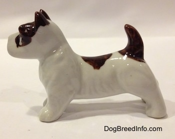 The left side of a white with brown bone china Jack Russell Terrier dog figurine. The figurine has short legs and a short body.