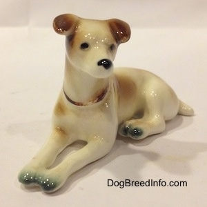 The front left side of a brown and white Jack Russell Terrier figurine. The figurine has a black circles for eyes.