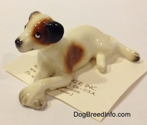 The front left side of a figurine of a white with brown and black Jack Russell Terrier dog in a lying down pose. The eyes of the figurine are very cartoon-y