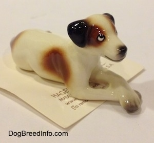 The front right side of a white with brown and black Jack Russell Terrier dog in a lying down pose figurine. The figurine has a black line for a mouth.