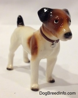 The front right side of a figurine of a white with brown and black Jack Russell Terrier dog. The figurine has short black ears that are hard to different from the head.