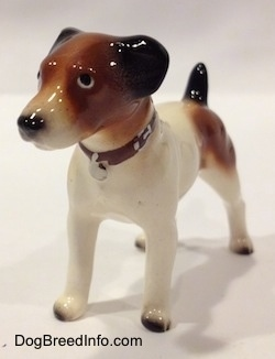 The front left side of a Jack Russell Terrier dog figurine. The figurines tails is in the air
