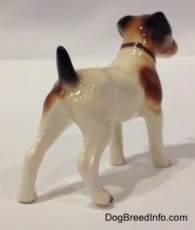 The back right side of a white with brown and black Jack Russell Terrier figurine. The figurine has long legs and it is glossy.