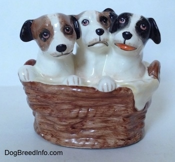 A figurine of three Jack Russell Terriers that are in a wicker basket. The figurine on the right has its mouth open.