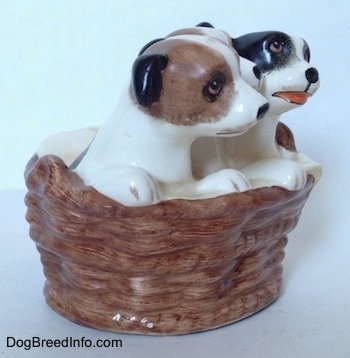 The right side of three Jack Russell Terriers that are in a wicker basket figurine. The figurines have short black ears.
