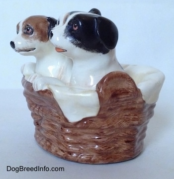 The left side of three Jack Russell Terriers that are in a wicker basket figurine. The figurines have there paws on the side of a wicker basket.