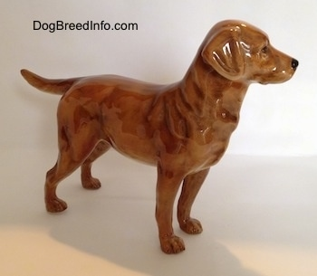 The right side of a figurine of a brown Labrador Retriever. The figurine has glossy ears that are flopped over.