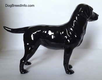 The right side of a black Labrador Retriever figurine. The figurine is glossy.