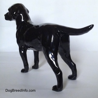 The back left side of a black Labrador Retriever figurine. The figurine has long legs.