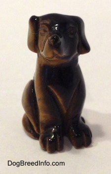 A Labrador Retriever figurine that is carved out of stone. It has a glossy nose.