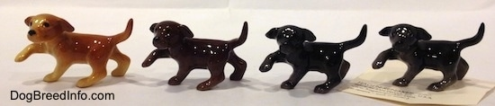 The left side of four Labrador Retriever puppy figurines in different color variations. The figurines have there right paws in the air.