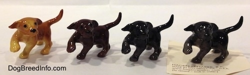 Four Labrador Retriever puppys in different color variation figurines with there paws in the air. The figurines are glossy.