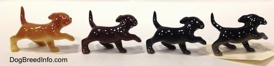 The right side of four Labrador Retriever puppy figurines in different color variations with there paws in the air.