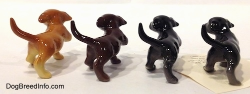 The back of four Labrador Retriever puppy figurines in different color variations.
