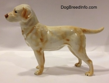 The left side of a yellow Labrador Retriever. The retriever has black circles for eyes. The figurine has small paws and longlegs.