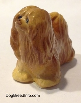 The front left side of a brown Lhasa Apso figurine. The figurine has short legs.