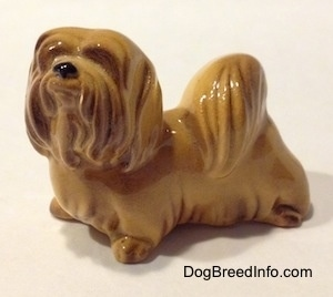The front left side of a Lhasa Apso figurine. The figurine has fine hair details.