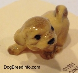 The front left side of a figurine of a Lhasa Apso puppy that is in a walking pose. The tail of the figurine is curled up on its back.
