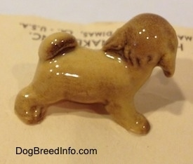 The right side of a brown figurine of a Lhasa Apso puppy. The ears of the figurine are hard to differentiate from the head.