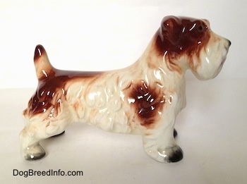 The right side of a white with brown figurine of a Lucas Terrier. The figurine has brown spot on its right side and one at the end of its tail.