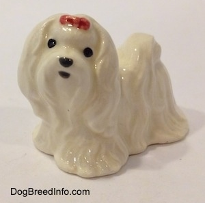 The front left side of a white Maltese figurine with a red ribbon in its hair. The figurine has black circles for eyes and a nose.