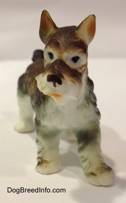 A bone china figurine of a grey and white Miniature Schnauzer. The figurine has black circles for eyes and its mouth is painted open.