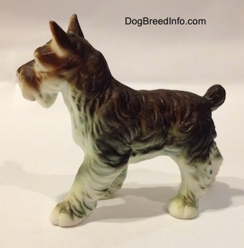The left side of a figurine of a grey and white bone china Miniature Schnauzer. The figurine has fine hair details along its body and legs.