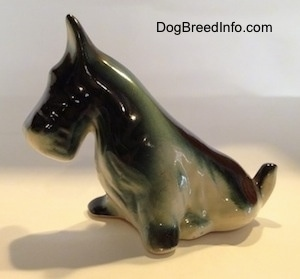 The front left side of a figurine of a black, gray and white miniature Schnauzer sitting. The figurine black ears.