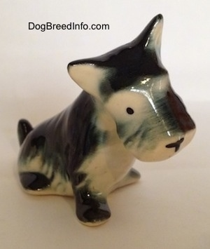 A black, gray and white ceramic Miniature Schnauzer figurine that is in a sitting position. The figurine has black circles for eyes.
