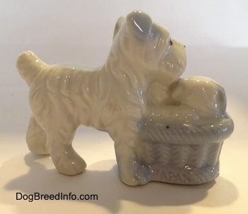 The back of a bone china Miniature Schnauzer with a basket of puppies next to her. The figurines have fine hair details.