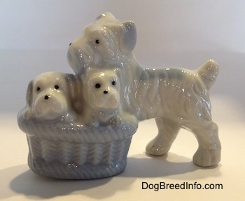 A figurine of a bone china Miniature Schnauzer dog next to a basket of her puppies. The basket is very detailed.