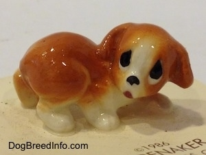 An orange and white puppy figurine that has big sad eyes.