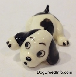 A white with black puppy figurine that is in a lying pose. The figurine has big black circles for eyes.